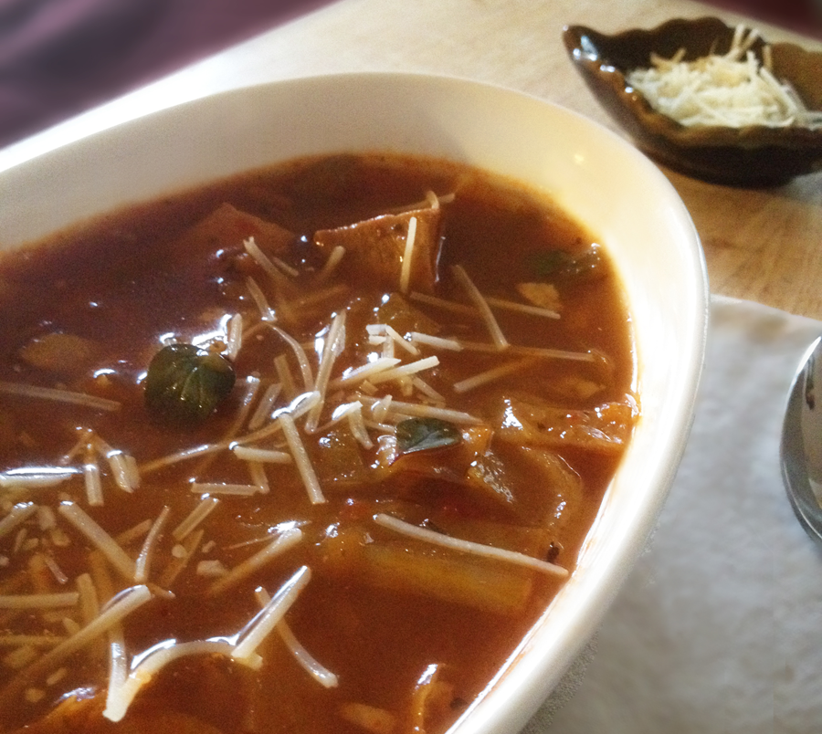 Tomato Cabbage Soup with Turkey served in a deep bowl and agrnished with parmesan cheese and fresh herbs.