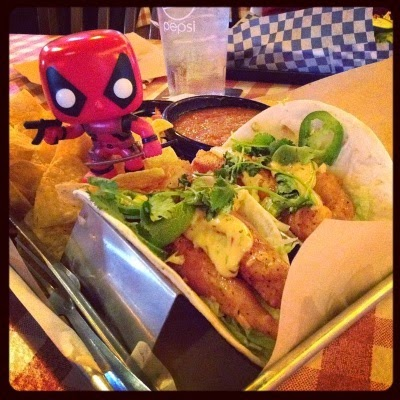 Tiny Deadpool stands in a pile of tortilla chips. In front of him, two taco stands hold seared catfish tacos topped with jalapenos, cilantro, and pale remoulade.