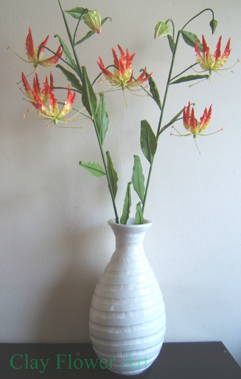 Climbing lily gloriosa clay flower art gloriosa is the state flower of tamil nadu also known as senganthal malar in tamil it is found in tropical africa and asia and are adapted to summer izmirmasajfo