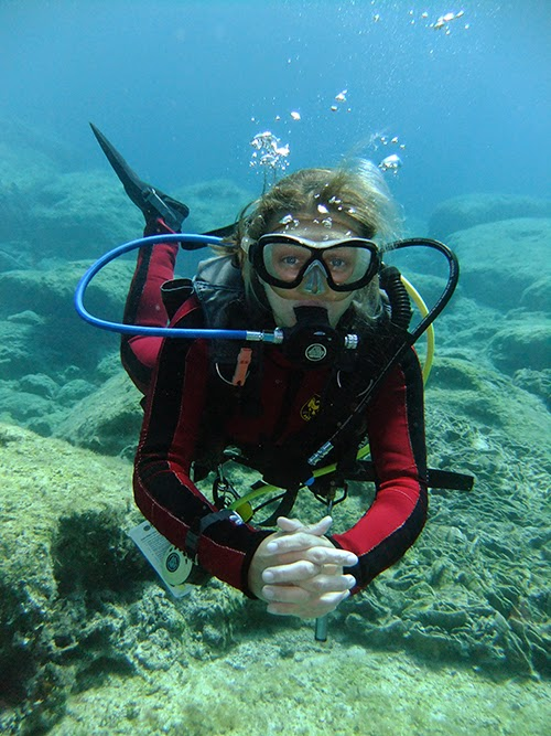 scuba diver hovers in good trim position over a rocky floor under the sea