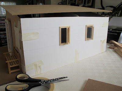 Rear view of a taped-together modern dolls' house miniature kit, with a cardboard wall and two small windows inserted.