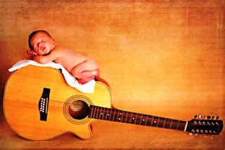 Gambar bayi lucu tidur di atas gitar