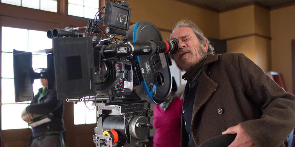 tommy lee jones como diretor de cinema operando uma câmera cinematográfica no set do filme divida de honra