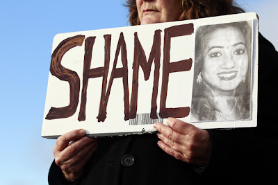 An Irish protester over Savita Halappanavar's death, caused by being denied an abortion, holds a sign that reads 