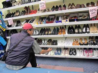 Man looking at shoes in the shoe section of Vinnies' Queanbeyan op shop/