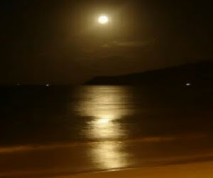 Foto da lua cheia refletindo na agua do mar