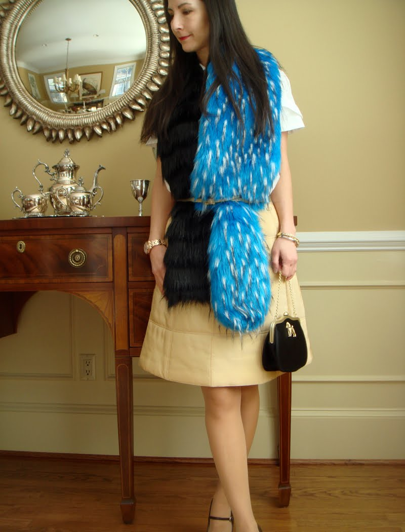 Fur scarf belted, black bag with dog hanging from hand.