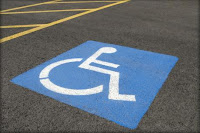 Photo of a disability parking space, focused on the painted wheelchair symbol and lines