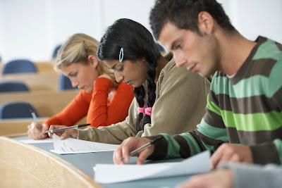 image of three students working on homework in a classroom.