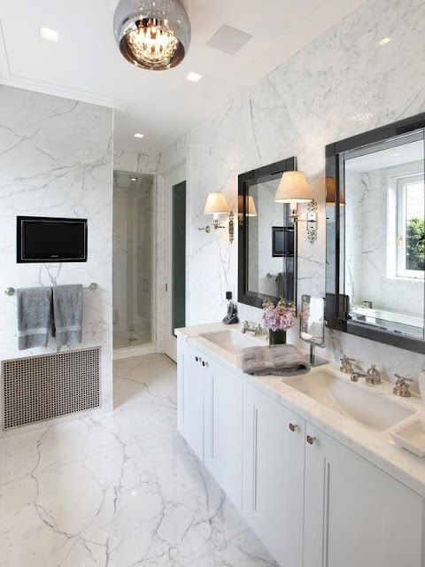white marble master bathroom in an apartment with built in white cabinets, black mirrors and undermount sinks