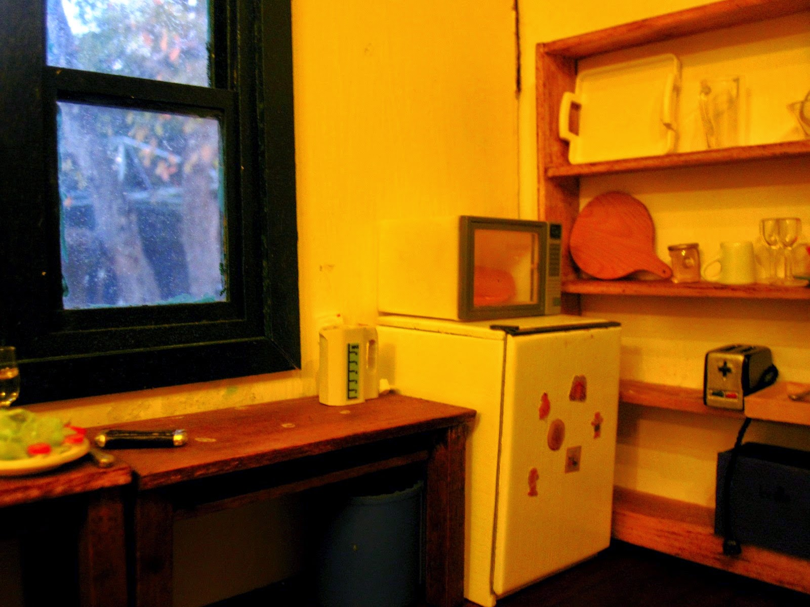Modern miniature scene of a holiday house kitchen at night, with a bar fridge, microwave and shelving holding various items of crockery and kitchenware.