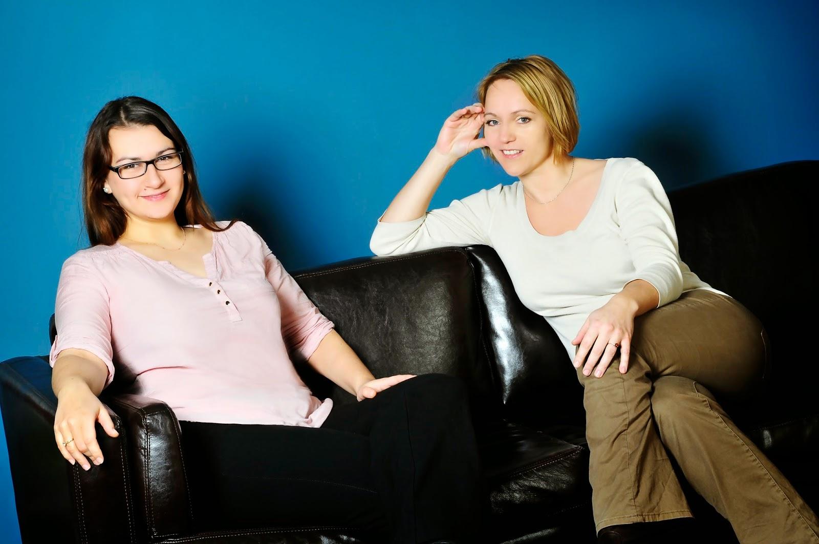 Ulrike Loth und Inga Sarrazin sitzen gemeinsam auf einer schwarzen Couch und lächeln freundlich in die Kamera.