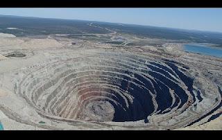 O homem é capaz de alterar de maneira drástica as paisagens pelo mundo. Um caso desses se aplica à chamada República da Iacútia, na Rússia. Ali foi escavado um imenso buraco, em um estado cujo imenso território é escassamente habitado, com 40% de sua área a norte do Círculo Polar Ártico e coberta de permafrost.  O buraco na foto acima é da mina de diamantes de Udachnaya, com 600 metros de profundidade, o que a torna a mais profunda do mundo na exploração dos brilhantes. Ela foi descoberta em 15 de Junho de 1955 e é responsável por 90% da produção dos brilhantes na Rússia e 27% do mundo.