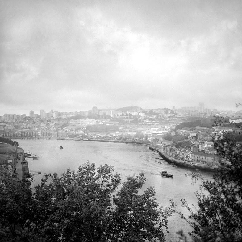 Foto a preto e branco, com câmara antiga, revelando em primeiro plano a folhagem das árvores do jardim do Pálacio de Cristal, dois barcos no rio e ao fundo a cidade de Gaia envolta na neblina típica desta zona