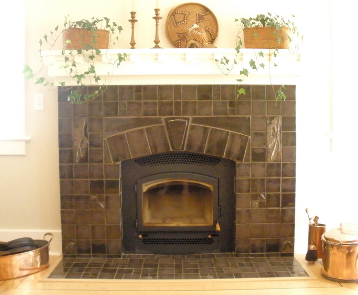 arts and crafts fireplace with hand made tile with pine branches boughs and cones