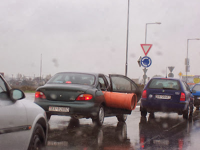 Un énorme tuyau dépasse d'une voiture, chargement dangereux.