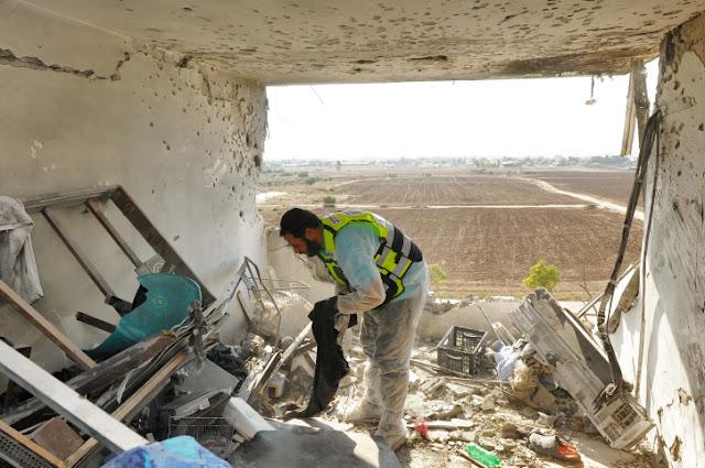 Een vrijwilliger in het appartement in Kiryat Malachi waar donderdag drie doden voelen, op zoek naar overblijfselen.