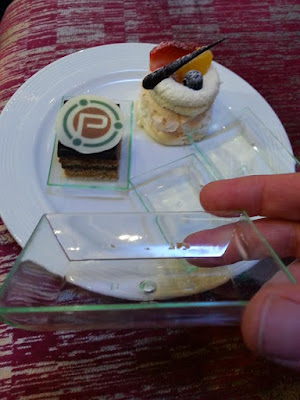 Plate with two small cakes on it. One is on a clear plastic tray. In the foreground is a hand holding up another of the trays.