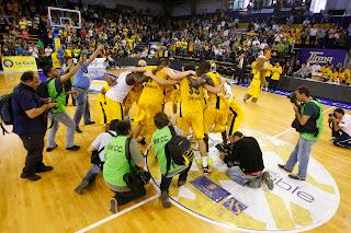 Los jugadores del Gran Canaria festejan en coro la victoria con los fotógrafos de la prensa alrededor - ACB PHOTO