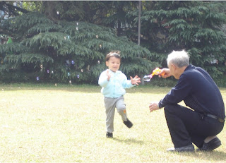 Boy and grandfather playing with soap bubbles, Shanghai 2008
