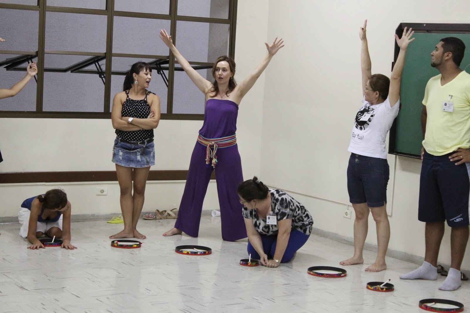 Descrição da Foto: Parte dos participantes estão lado-a-lado, com o tambor na frente no chão. Eles estão posicionados em três posições: baixo, médio, alto.