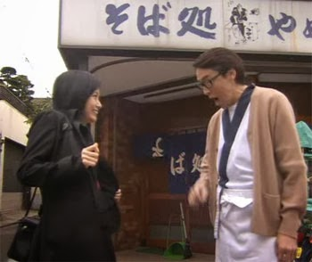 Misaki and Wakamura's father in front of the soba shop.