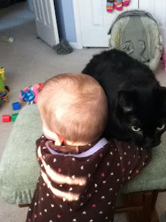 Baby hugging a black cat