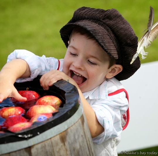 Cameron Huckle, 3, Napier, apple bobbing at Shakespeare in the Park, at Church Rd Winery, Taradale, Napier photograph