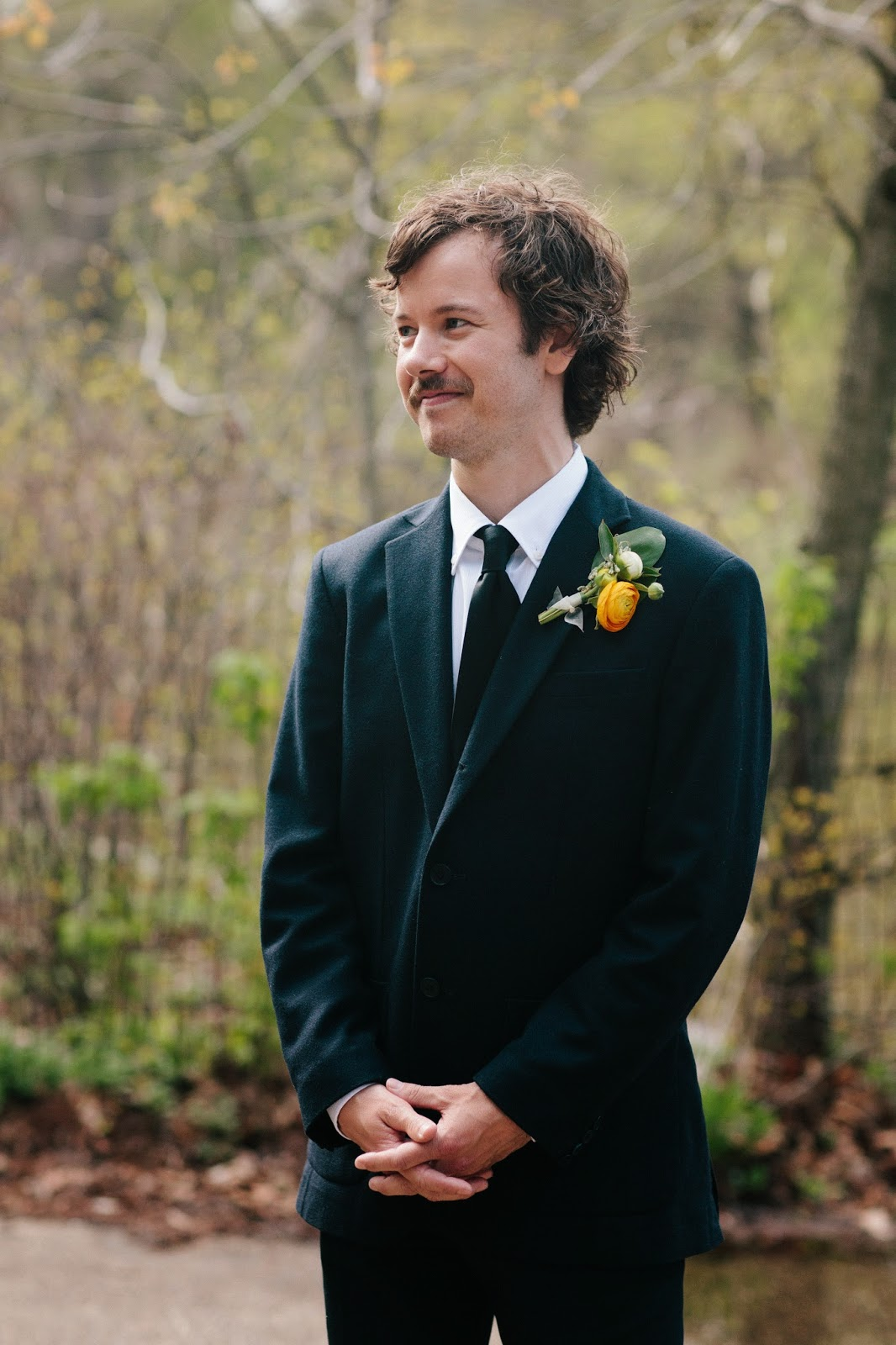 groom in a navy suit and black tie with a yellow ranunculus spring boutonniere