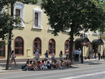 Зрители сидят в тени деревьев на поребрике улицы Кремлевской
