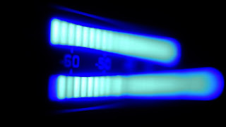 A cool blue LED glow of audio meters rhythmically pulse high and low