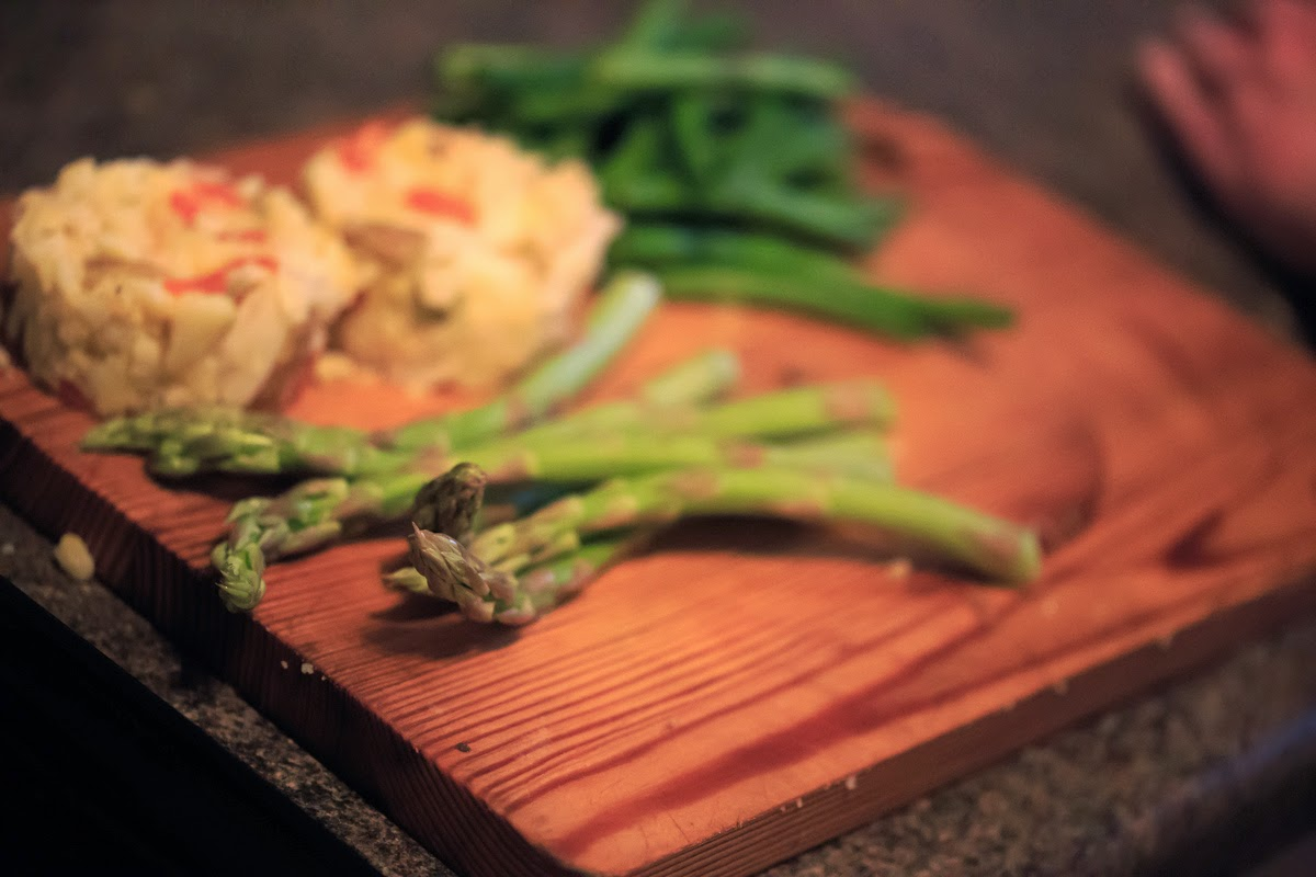 Asparagus, green beans and potato cakes on a wooden board