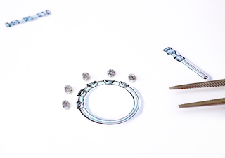デザイナー岡田訓明が描いたデザイン画の上にダイヤを並べて確認しているところの写真