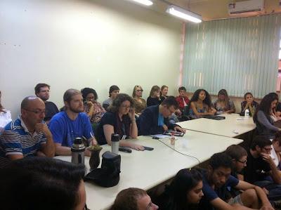 A foto mostra uma sala de reuniões com professores representantes do movimento: Marco Bonito, Joseline Pipi, João Antonio, dentre outros 13, sentados em uma mesa e cercados por estudantes e técnicos administrativos que também participaram da vídeo conferência com outros campi da Unipampa.