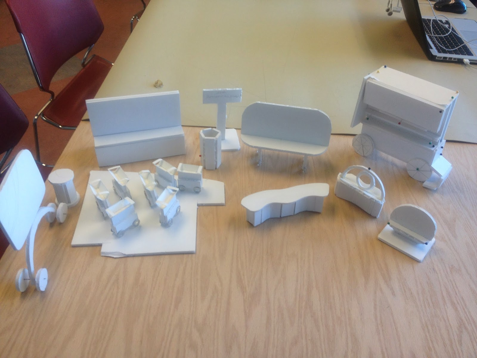 A frontal view from eye level of a group of foam core model mockups on a table.