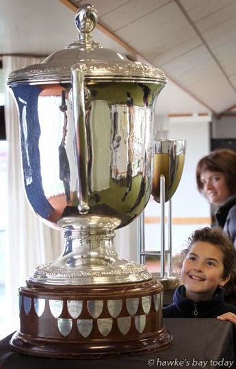 Front: Jessica Joe-Harrison, 9, Napier, with the Bledisloe Cup and the Investec Rugby Championship Cup, on public display at Mclean Park, Napier photograph