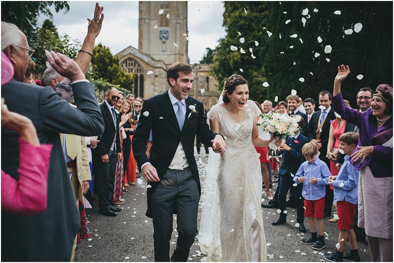 Bride and groom walk under rose petal confetti