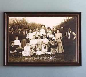 """The image to the left is a family photo of the owner/brewer, Janet. Janet's grandmother is a baby in the photo, and her great grandmother is the woman who brewed the barrel of beer shown. Written on the original photograph are the words """"What is home without beer?"""" This hangs on the wall in our taproom, come visit us to see it and ask Janet more about her long history with brewing!"""