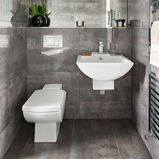 Baños Grises Pequenos:El área del WC y lavabo están bajo un espejo rectangular como se