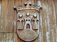 L'escut de Gurb esculpit en fusta sobre els batents del portal principal de la Rectoria