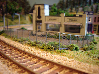Completed and installed scratch-built HO scale chain link fence