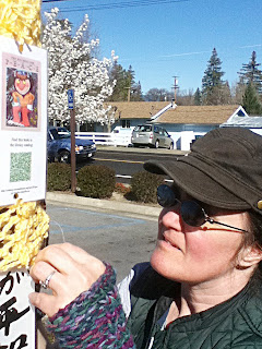 Cynthia Parkhill attaches yarnbombing tag to peace pole at Lakeport Library