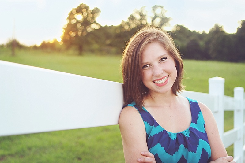 The Persimmon Perch - Senior Pictures Backlit at Sunset with fence rail