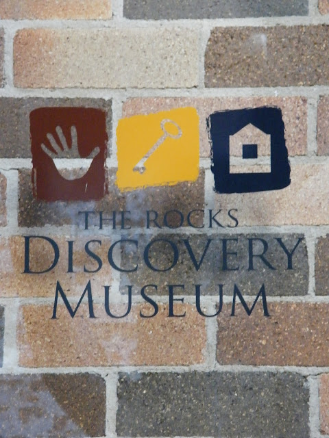 The Rocks Discovery Museum sign and logo on the entrance door