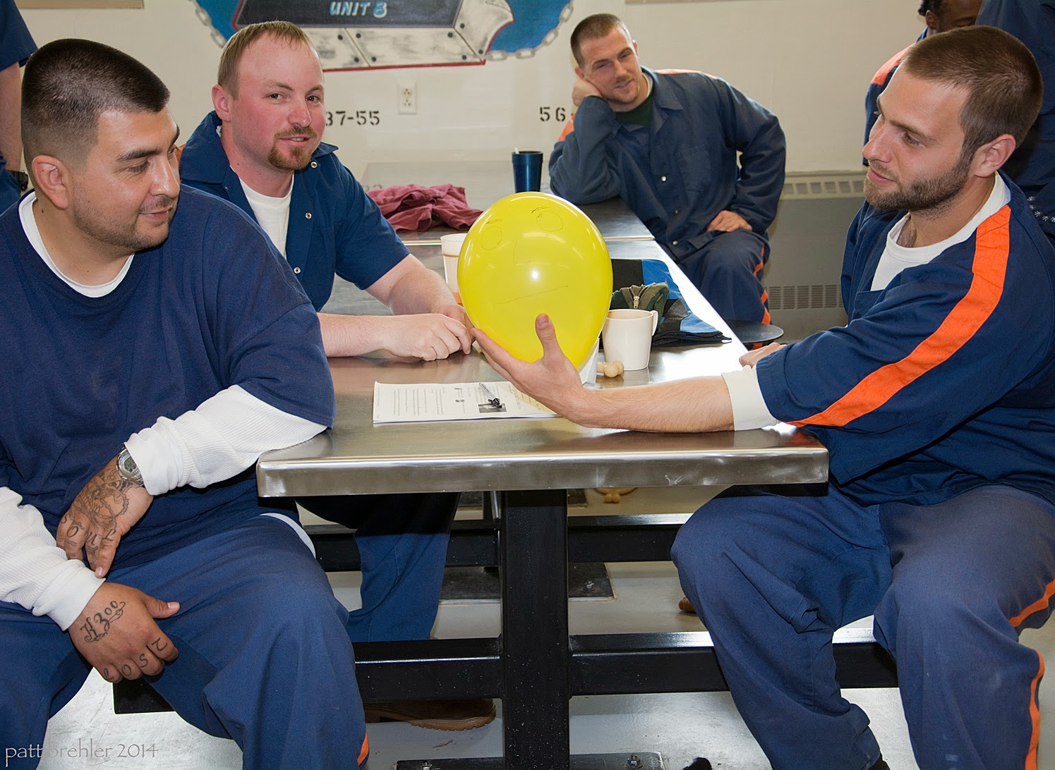 Four men dressed in the prison blue uniforms sit around a lunch table. The man on the right is holding a yellow balloon in his left hand on the table and looking at it. The man on the left has his left elbow on the table and is looking at the balloon. The two men in the background are looking at the camera and smiling.