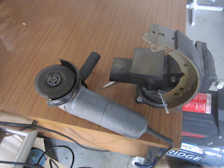 Taking off the sharp edge of the brake lining with a grinder