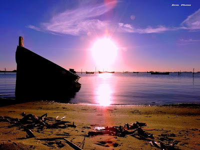 Belo por do sol com barco de pesca na lagoa