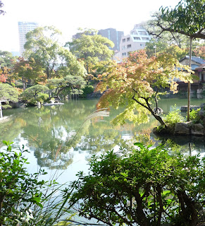 Pretty little japanese pond with lots of trees a small woodern house and some city buildings in the background at the Sorakuen gardens, Kobe