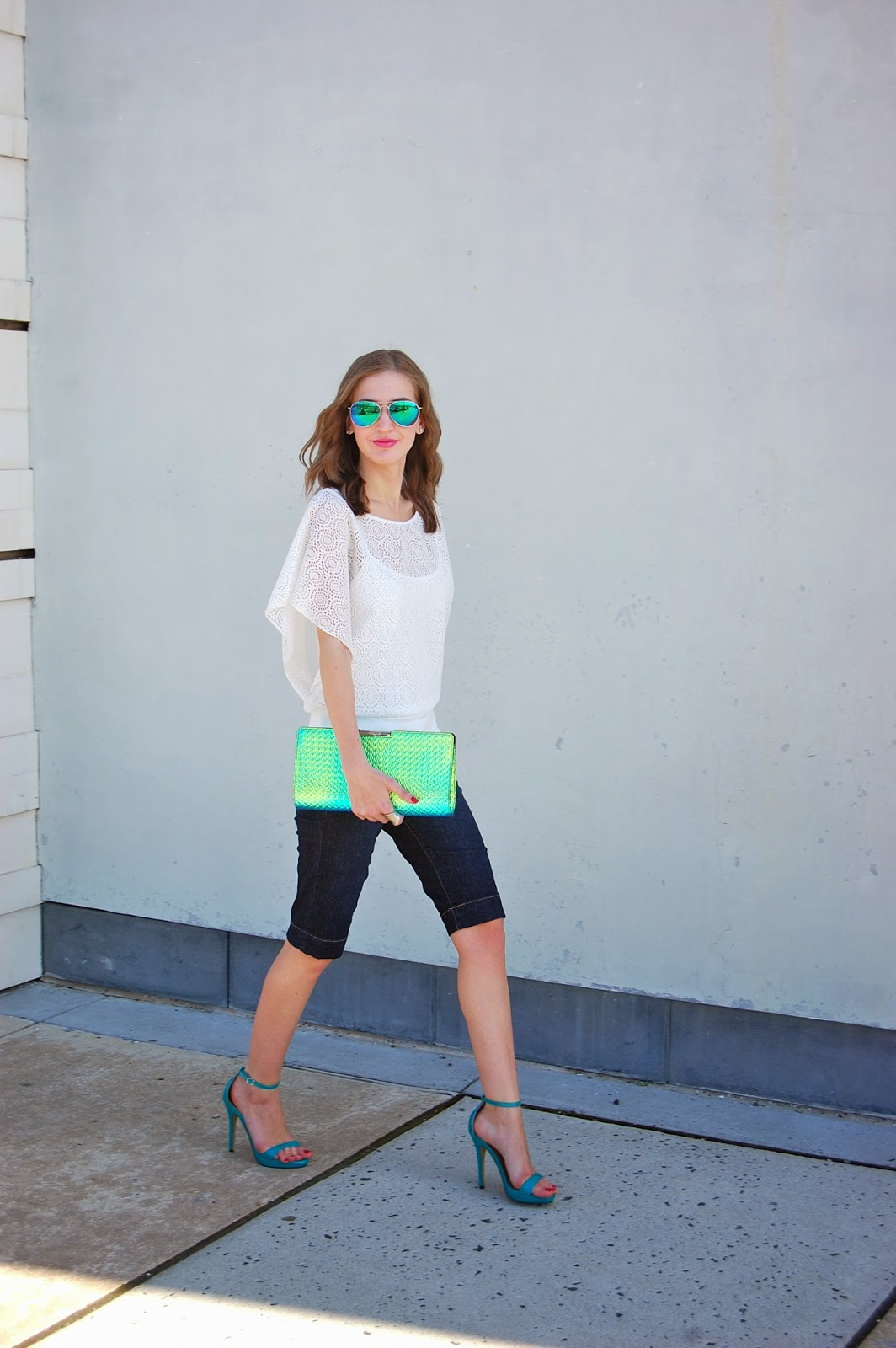 Wearing denim bermuda shorts, spring summer 2014 trends, Michael Antonio lovina sandals, Milly Miley frame clutch in embossed hologram and mirrored sunglasses