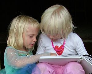 Sisters reading a book together - Stock Photo Credit: hortongrou